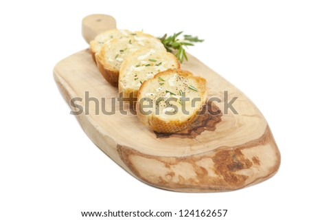 Close up image of slices of baguette bread with garlic spread and pepper on wooden board
