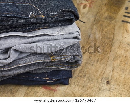 Close up image of stack of folded men\'s jeans on wooden table