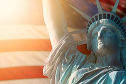 CLOSE UP IMAGE OF STATUE OF LIBERTY WITH BLUR AMERICAN FLAG IN BACKGROUND