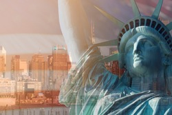 CLOSE UP IMAGE OF STATUE OF LIBERTY WITH SKYSCRAPER BUILDINGS IN NEW YORK AND BLUR AMERICAN FLAG IN BACKGROUND, NEW YORK, USA /DOUBLE EXPOSURE