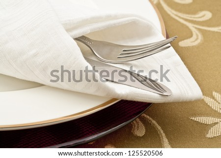 Close up image of table setting with knife, fork , napkin and plate #125520506
