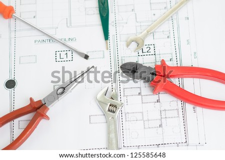 Close-up image of technical tools lying arranged over a blueprint