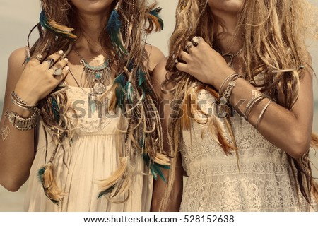 Photo of close up image of two hippie girls. boho style accessories