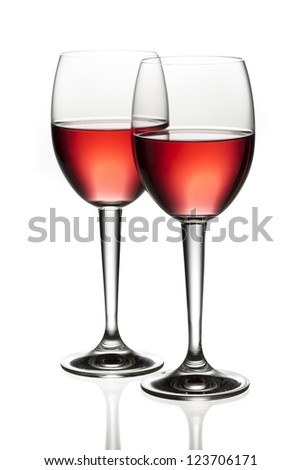 Close-up image of two red wine toasting each other over white background