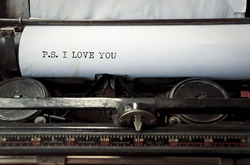 close up image of typewriter with paper sheet and the phrase: p.s. i love you. copy space for your text. retro filtered