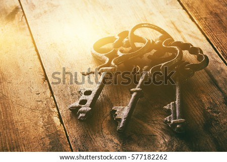 close up image of vintage skeleton keys over wooden table and bright light as revelation concept