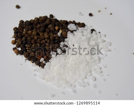Close-up image of white rock salt and black pepper on white background - image