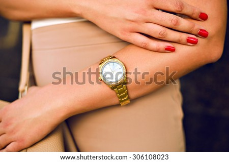 Close up image of woman hand, with stylish gold classic watches, fashion details, young businesswoman, beige golden colors.