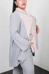 Close up image of woman in grey summer spring suit. Fashion clothes for overweight plus size females. High key cropped image with copy space. Body positivism. Hands in pocket