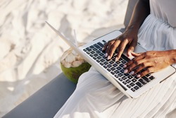 Close-up image of woman sitting on sandy beach and working on laptop, coding or answering e-mails