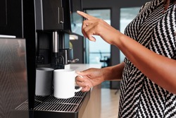 Close-up image of woman using espresso machine when making big mug of coffee in office kitchen