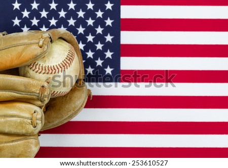 Close up image of worn leather mitt and used baseball with United States of America flag in background. Concept of baseball sport in America.