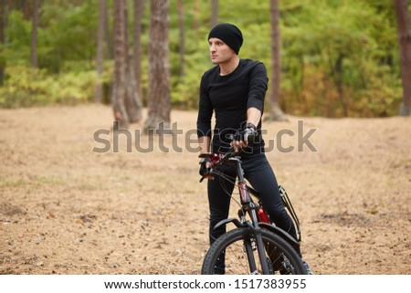 Photo of Close up image of young man standing near his bike on forest road, stops to have rest, riding bike on weekends, spending free time, active male wearing sportwear and cap, looking aside. Sport concept.