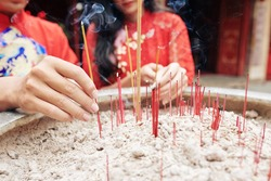 Close-up image of young people putting smoking sticks in copper urn in Buddhism temple on Lunar New Year