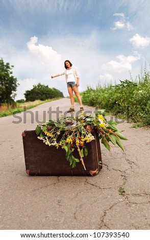 Close up image old suitcase on the road with girl - auto-stop traveler