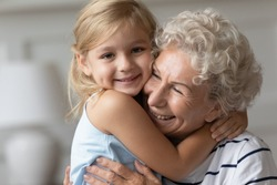 Close up image portrait happy small cutie granddaughter hugging with caring old grandmother, multi generational family relatives people snuggle to each other feeling love and strong connection concept