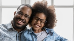 Close up image portrait of cheerful african father and little daughter with wide toothy healthy white smile wearing trendy stylish eyeglasses, advertise dental services or eyewear store offer concept