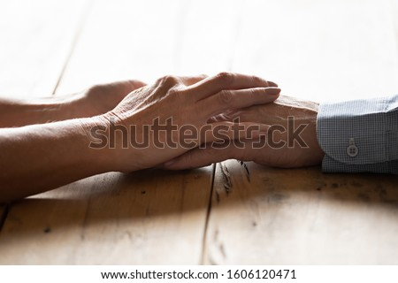 Close up image spouses sit at wooden desk holding hands feeling love and strong attachment wife and husband arms together as symbol of honesty, heart-to-heart talk, give support to loved one concept
