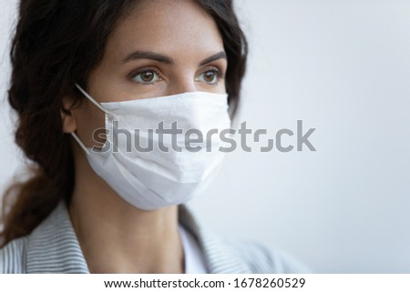 Close up image woman in facial medical mask on blue background, concept of protection to globally spread pandemic infection disease coronavirus or COVID-19 illness that affect your lungs and airways