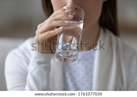 Close up image woman sit indoors holds glass of still or mineral water drinking clean aqua reducing thirst. Healthy lifestyle life habits, enough quantity every day for beauty skin health care concept