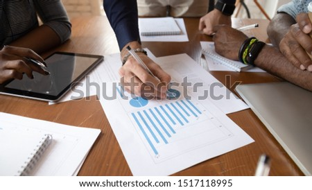 Close up image young businessman holding pen, editing paper documents with printed documents, explaining marketing strategy or planning company economic growth at brainstorming meeting at office.