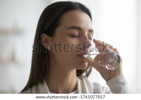Close up image young pretty woman holding glass drink enjoy aqua makes gulp of clean natural water reducing thirst caring about health and beauty, healthy lifestyle and enough liquid intake concept
