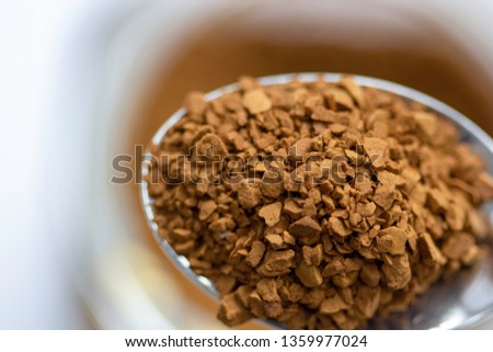 Close-up images of roasted instant coffee granules in a spoon with blury background.