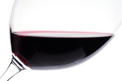 Close-up in the backlight of a wine glass with red wine