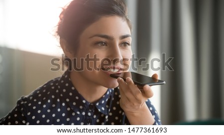 Close up indian woman hold smart phone talking on speakerphone through microphone with client, using translator application, internet services through virtual assistant or record audio message concept