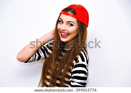 Stock Photo Close up indoor fashion lifestyle portrait of cool pretty young brunette girl, amazing long hairs, bright makeup, red hat and stripy tshirt, amazing big smile, cute face, urban image with flash.