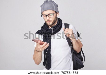 Close up indoor portrait of Caucasian male in trendy hat and white t-shirt holding mobile phone in hand looking attentively into screen, reading news online while standing on white wall background.