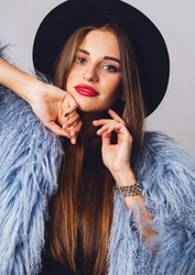 Close up indoor studio winter  fashion portrait of pretty young model in stylish blue  fluffy coat and black hat posing . Evening bright make up. Red lips.