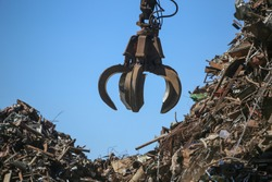 Close up industrial claw machine, move scrap metal in the landfill. Excavator arm, claw crane.