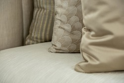 Close up interior design detail of silk cushions with a feathered pattern and gold textures on a silk couch.
