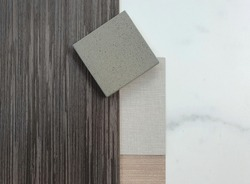 close up interior mood and tone of material board containing grey walnut veneer wood ,fabric and oak wood laminated ,artificial stone and marble tile samples.