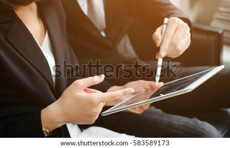 close up investor businesswoman hand finger point on tablet display for consult stock statistic graph with businessman for business technology concept.
