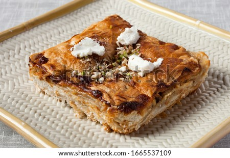 Close-up is Egypt's famous and traditional dessert Om Ali, Umm Ali or Oum Ali. Egyptian Bread Pudding. Arabic cuisine, Egypt culture concepts. Horizontal on white background. Stock photo ©