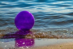 Close up isolated image of a plastic inflatable transparent beach ball left on the beach where waves hit the shore. The ball is backlit and sun light passing through casts a vibrant purple shadow.