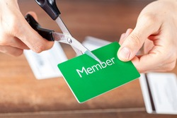 Close up isolated image of A young woman cutting a membership card. Customizable with copy space on the card. Suitable for cutting the costs, cancellation, termination of subscription and membership