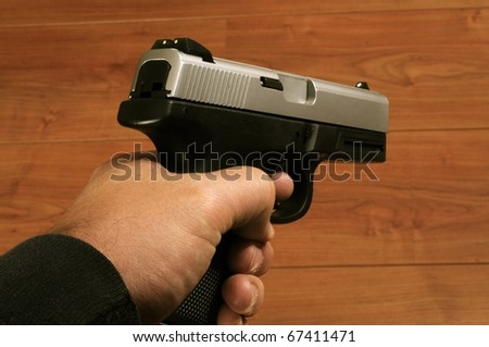 Close up isolated image of male holding pistol