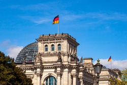Close up isolated image of the historical landmark building  Reichstag (Imperial Diet) in Berlin. Image shows the exterior of the historic architecture including the dome and two German Flags flying.