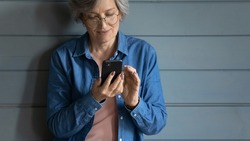 Close up isolated mature woman wearing glasses using smartphone, standing on grey wooden wall background, shopping or chatting with relatives online, browsing mobile device apps, generation and tech