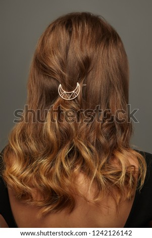 Close up isolated portrait of a lady with wavy ombre hair. The back view of the girl with half-up hairstyle, adorned with openwork golden crescent moon barrette. Posing over the grey background.