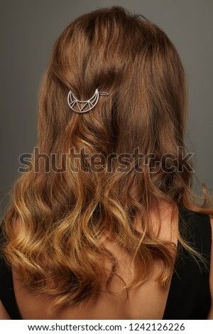 Close up isolated portrait of a lady with wavy ombre hair. The back view of the girl with half-up hairstyle, adorned with openwork silver crescent moon barrette. Posing over the grey background.
