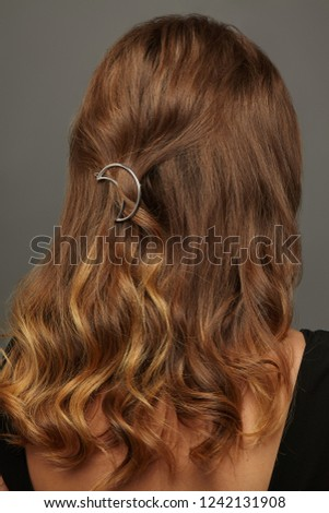 Close up isolated portrait of a lady with wavy ombre hair. The back view of the girl with half-up half-down hairstyle, adorned with silver crescent moon barrette. Posing over the grey background.