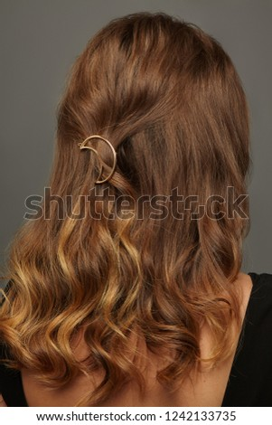 Close up isolated portrait of a lady with wavy ombre hair. The back view of the girl with half-up half-down hairstyle, adorned with golden crescent moon barrette. Posing over the grey background.