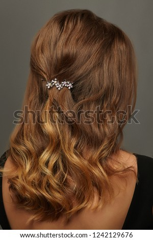 Close up isolated portrait of a young lady with wavy ombre hair. The back view of the girl with half-up half-down hairstyle, adorned with silver floral barrette. Posing against the grey background.