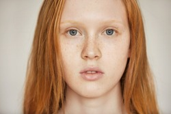 Close up isolated portrait of Caucasian teenage girl with long red hair, blues eyes and healthy freckled skin looking at the camera against gray wall background. Human face expressions and emotions