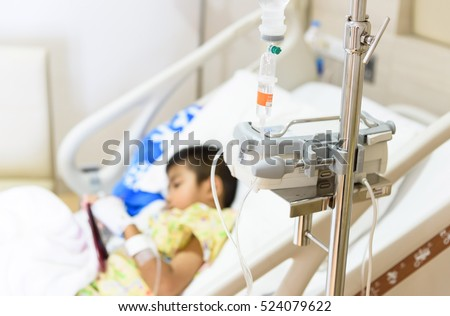 Close up IV set and blurry illness asian boy sleeping on hospital bed.Medical equipment concept.