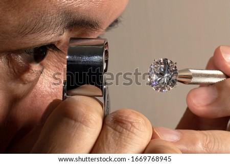 Close up jeweller asian man looking through loupe polished diamond. Diamond view. Diamonds grading.